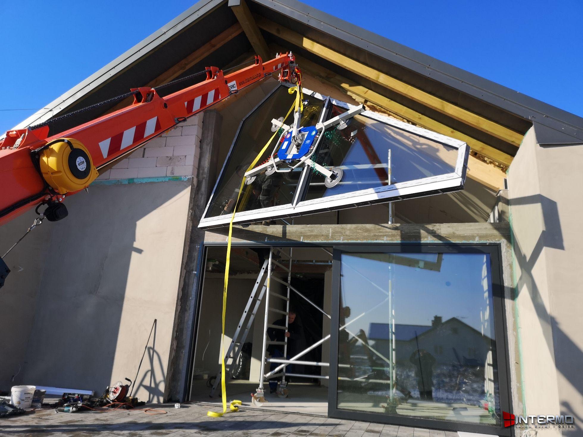 Dźwig podnosi okno do montażu